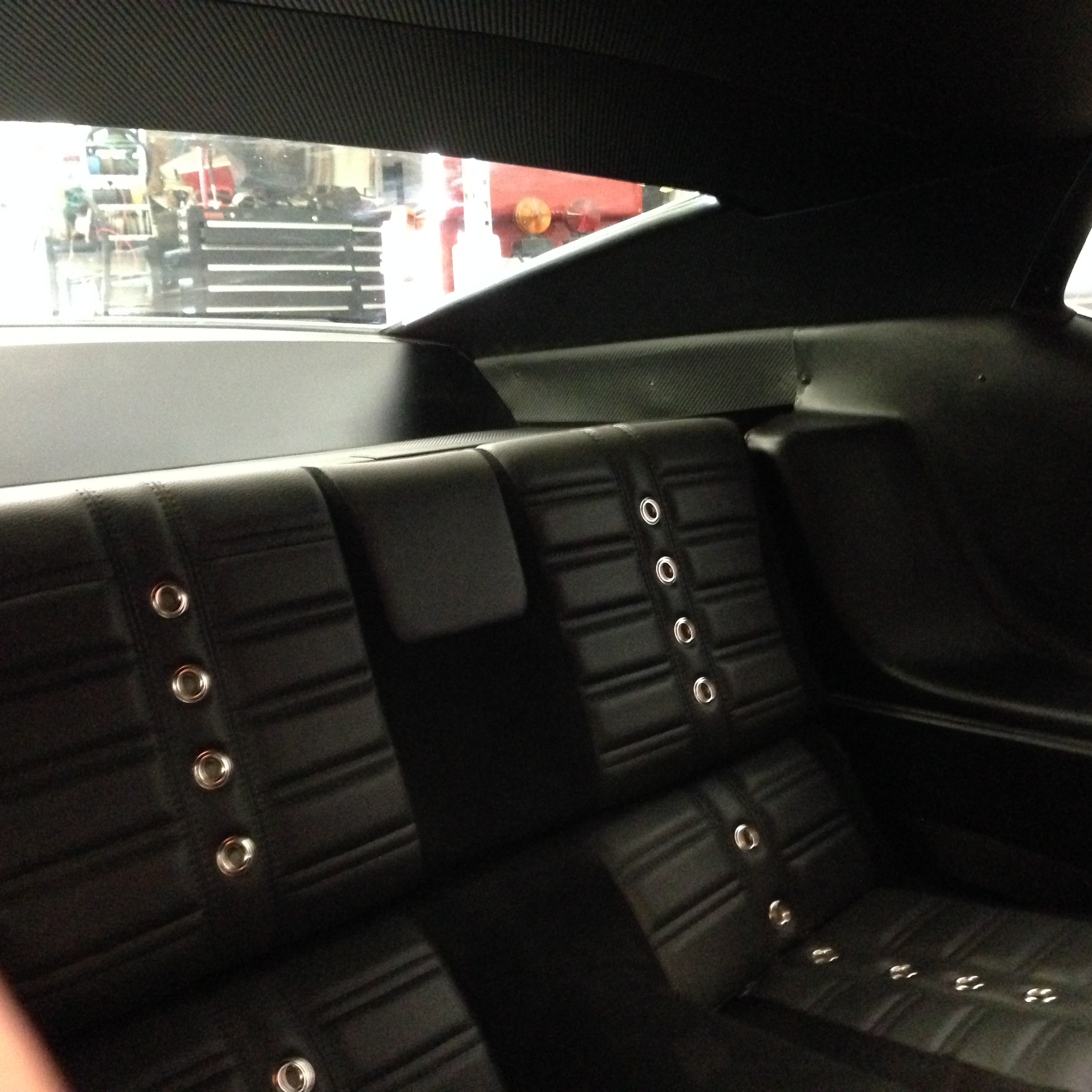 Rear seat with sail trim and package tray done in the carbon fiber vinyl that matches the headliner